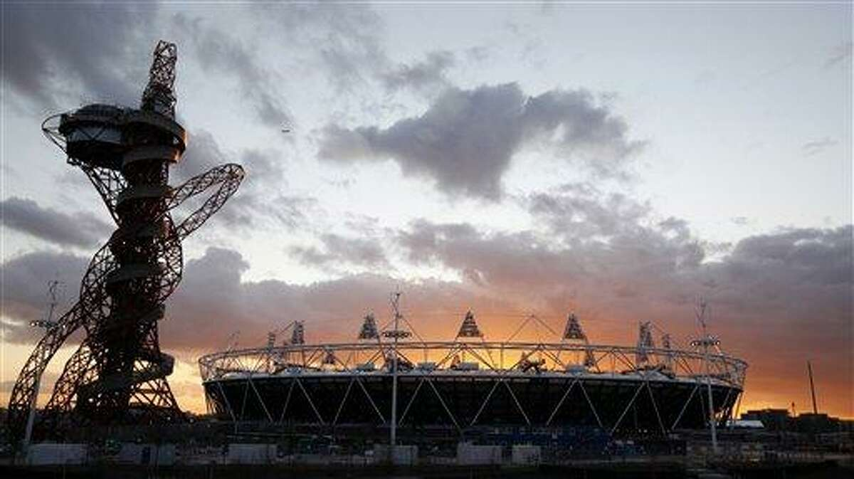 FILE This Wednesday, March 7, 2012 file photo shows the London 2012 Olympic Stadium at sunset at the Olympic Park in London. The 2012 Olympics will showcase a much different London and a much different event from the 1948 London Olympics which was hosted amid severe austerity in the aftermath of World War II. This will be a $14.5 billion extravaganza featuring multimillionaire professionals and global stars like Usain Bolt and Michael Phelps, shiny new purpose-built venues and a revitalized east London. Britain's biggest peacetime project also comes with a massive security operation. (AP Photo/Alastair Grant)