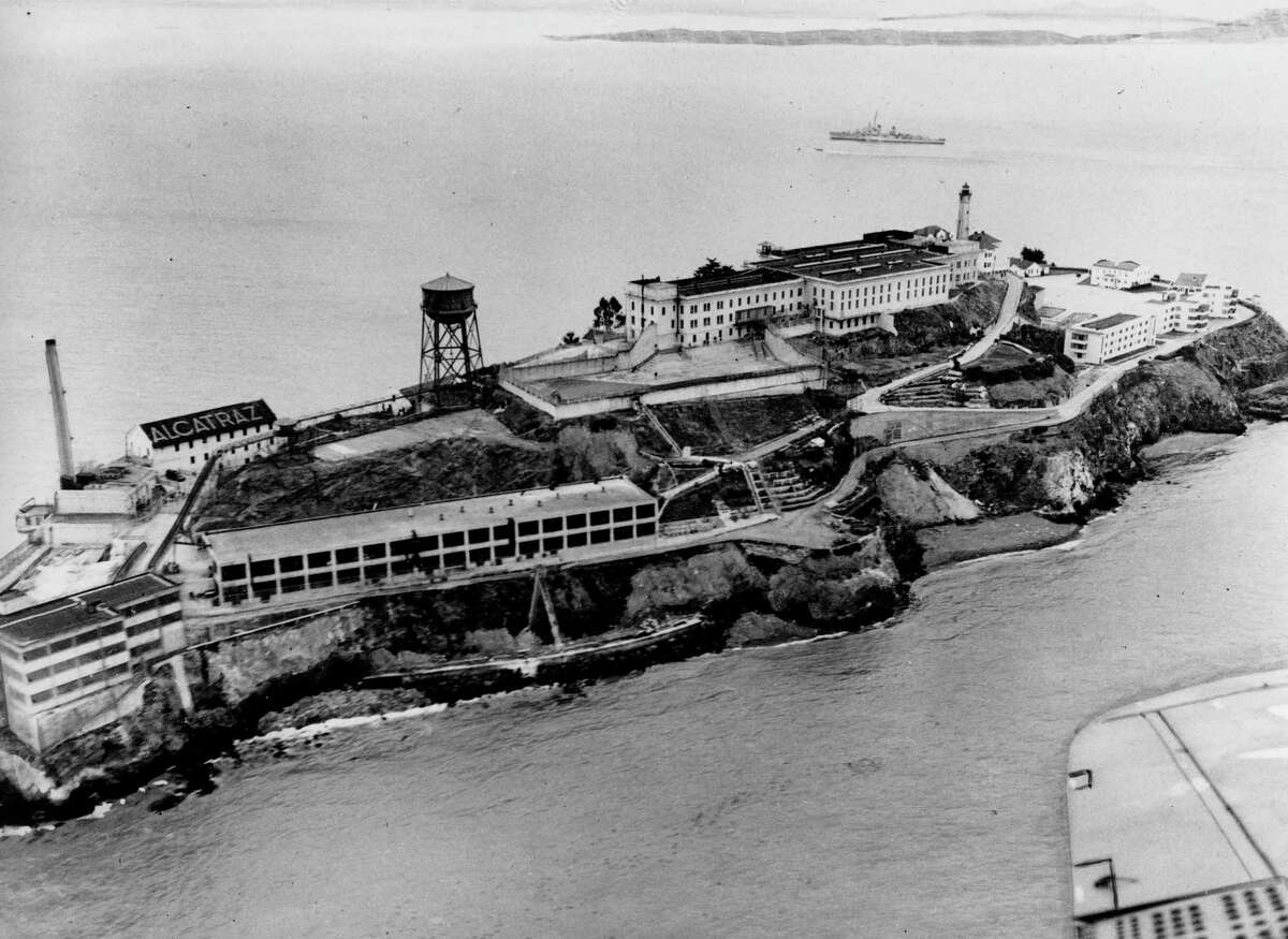 """This is an undated aerial view of the federal prison island Alcatraz, also known as """"The Rock,"""" in the San Francisco Bay, California. On the left are the facilities of the Model Industries buildings, up on the hill is the cellhouse with the high-walled recreation yard in front. (AP Photo)"""