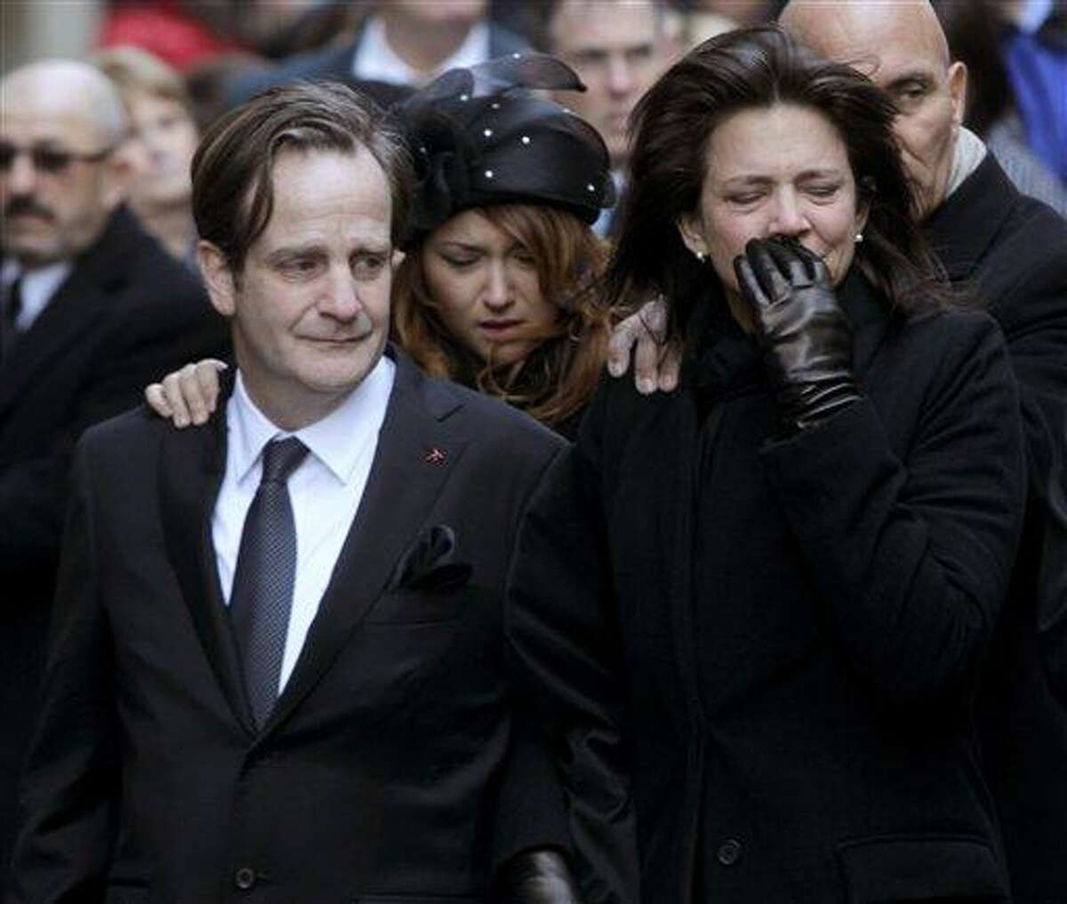 Matthew Badger, left, and Madonna Badger, the parents of three children that were killed in a fire, watch as their children's caskets are carried into a church during the funeral Jan. 5 in New York. Associated Press