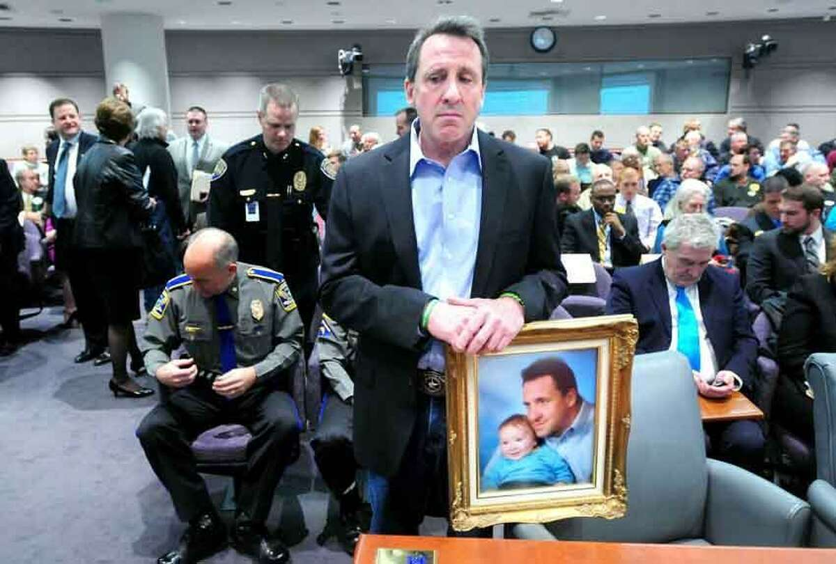 Neil Heslin of Shelton, holding a photograph of himself with his son Jesse Lewis, prepares to give testimony at a legislative hearing about gun control Monday at the Legislative Office Building in Hartford. His son was killed at the Sandy Hook shootings in December. Photo by Arnold Gold/New Haven Register
