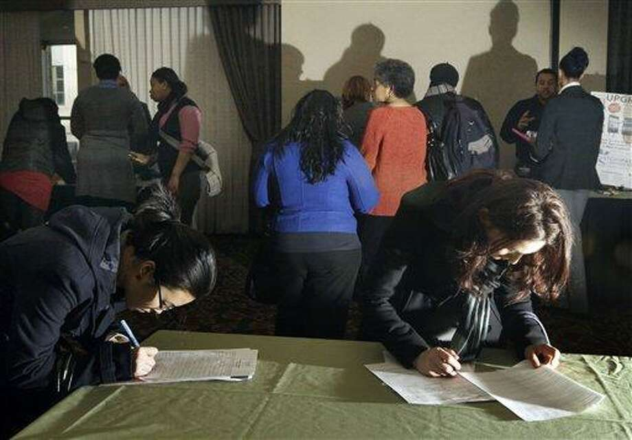 In this February photo, Peishan Wu, left, of Boston and Gerta Uruci-Limani, right, of Quincy, Mass., fill out applications as other job seekers crowd around tables at a job fair in Boston.  Associated Press Photo: AP / Copyright: The Associate Press