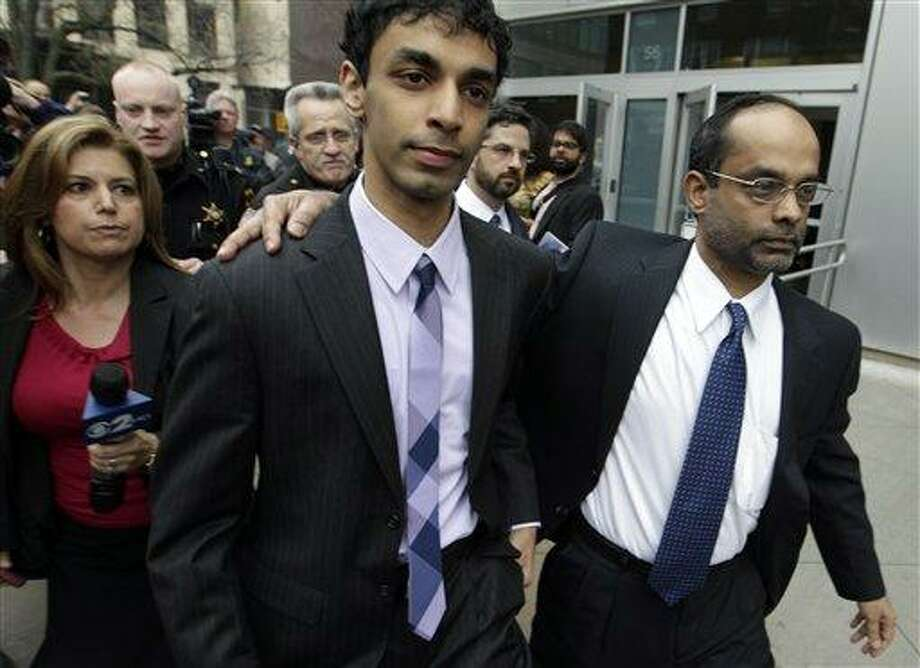 Dharun Ravi, left, is helped by his father, Ravi Pazhani, right, as they leave court in New Brunswick, N.J., March 16. Ravi, a former Rutgers University student accused of using a webcam to spy on his gay roommate's love life, has been convicted of bias intimidation and invasion of privacy. Associated Press Photo: AP / AP