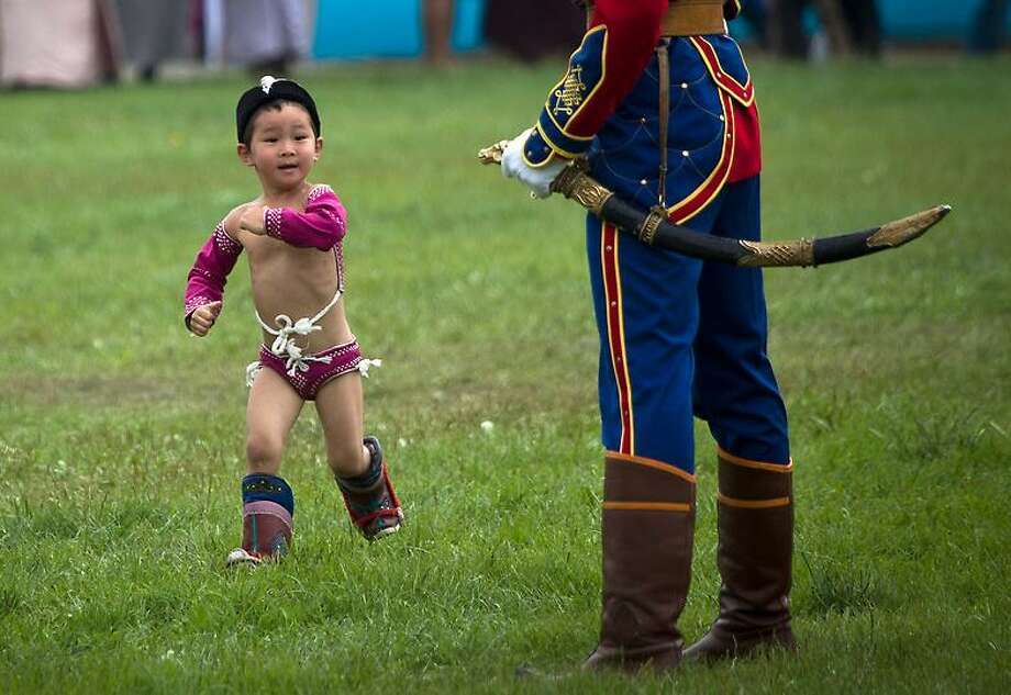 A Mongolian boy in costume runs past a member of guard of honor during the Naadam Festival in Ulan Bator, Mongolia Wednesday, July 11, 2012. Mongolians celebrate the anniversary of Genghis Khan's march to world conquest on July 11 with the annual sports festival featuring traditional Mongolian events including wrestling, archery, and horse racing. (AP Photo/Andy Wong) Photo: ASSOCIATED PRESS / AP2012