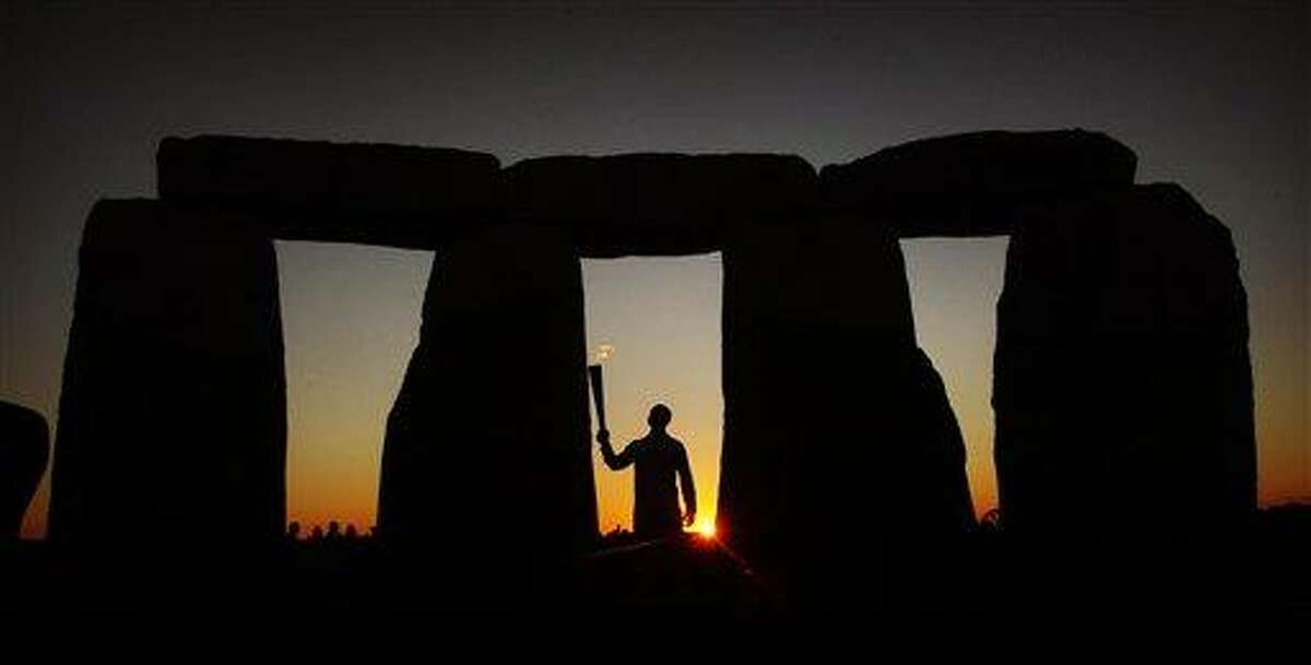 This image, made available by LOCOG, shows U.S. Olympian sprinter torchbearer Michael Johnson holding the Olympic flame at Stonehenge, England, Thursday. The Olympic Torch is being carried around England in a relay of Torchbearers to make its way to the London 2012 Olympic Games opening ceremony. Associated Press