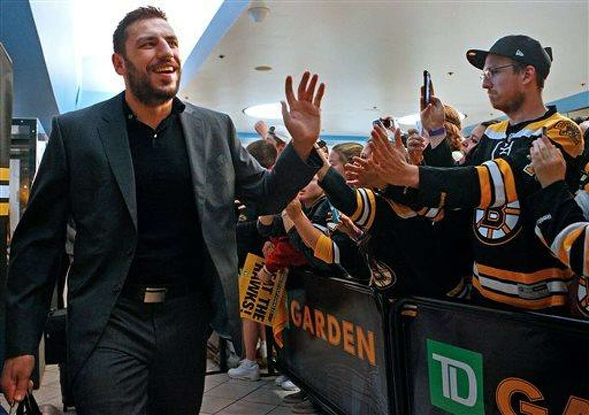 Boston Bruins left wing Milan Lucic high fives fans as the NHL hockey team departs the TD Garden in Boston for Chicago on Tuesday, June 11, 2013. The Bruins are scheduled to face the Chicago Blackhawks in Game 1 of the Stanley Cup finals on Wednesday. (AP Photo/The Boston Herald, Nancy Lane)