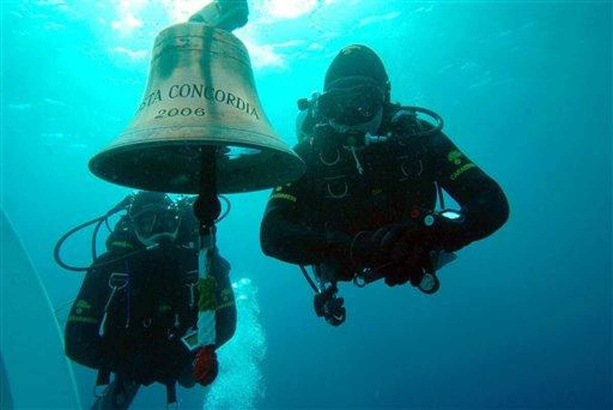 In this undated underwater photo, released by the Carabinieri (Italian paramilitary police) Friday, two Carabinieri scuba divers swim next to the Costa Concordia cruise ship's bell, off the tiny Giglio island, Italy. Associated Press