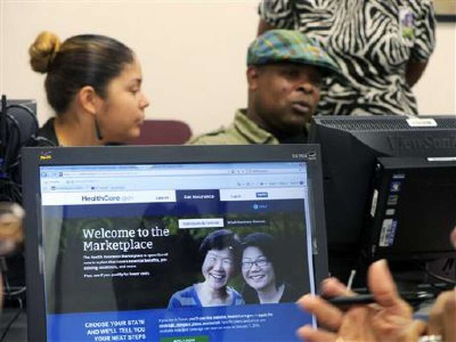 Parkland Memorial Hospital financial counselor Tiffany Ruiz, left, helps Vyncent Bosh sign up for insurance under the Affordable Care Act in Dallas. (AP Photo/The Dallas Morning News, Ron Baselice) Photo: AP / The Dallas Morning News