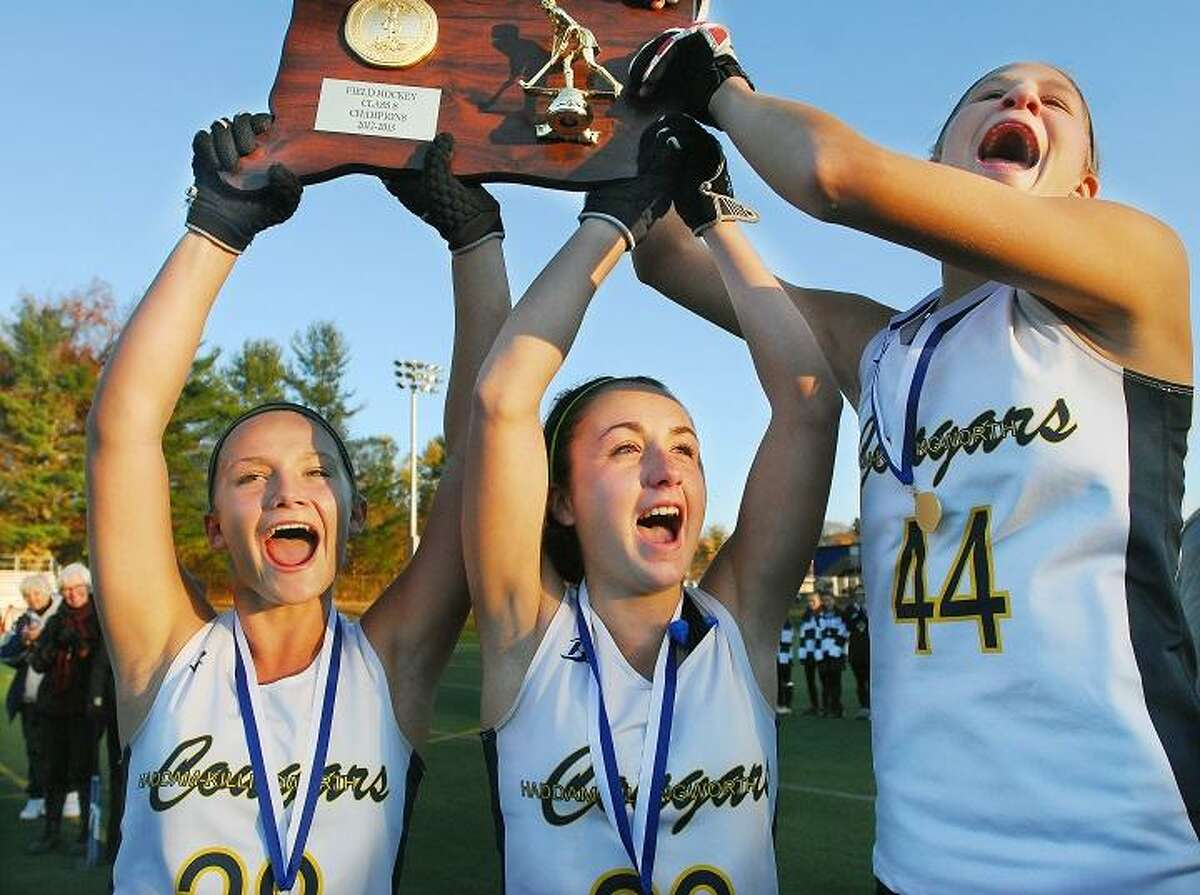 Catherine Avalone/The Middletown Press H-K senior captains Sam Waskowitz, Marissa Moncata and junior captain Kiley Anderson raise the Class S CIAC State Championship plaque in the air after defeating Stonington at the Joseph F. Cottone Field at Wethersfield High School to win the state title.