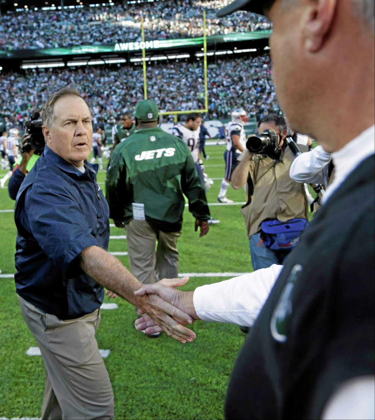 New England Patriots head coach Bill Belichick shakes hands with New York Jets head coach Rex Ryan after Sunday's game in East Rutherford, N.J. The Jets won the game 30-27.