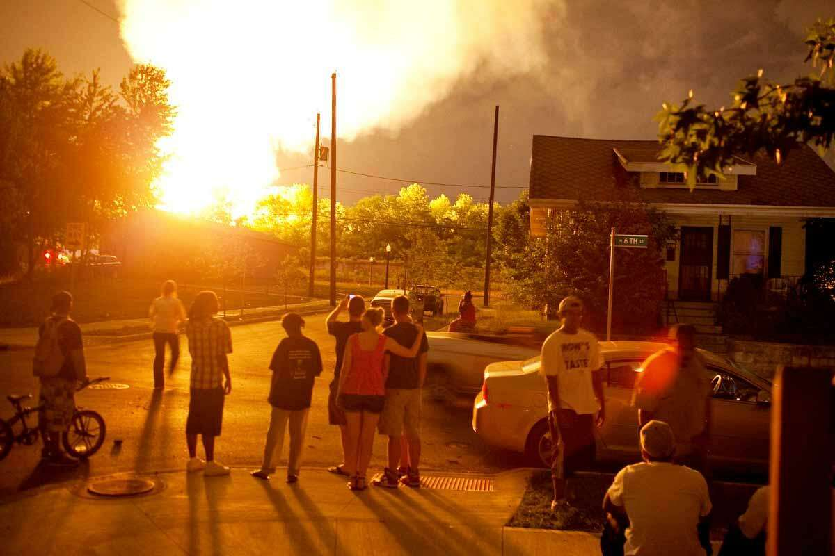 People watch the flames shoot up from a freight train that derailed and some cars burst into flames, early Wednesday morning July 11, 2012 in Columbus Ohio. Lt. Terry Bush says the accident happened at about 2 a.m. Wednesday in a mixed-use part of the city, and people living in one-mile radius of the blast have been evacuated. Associated Press