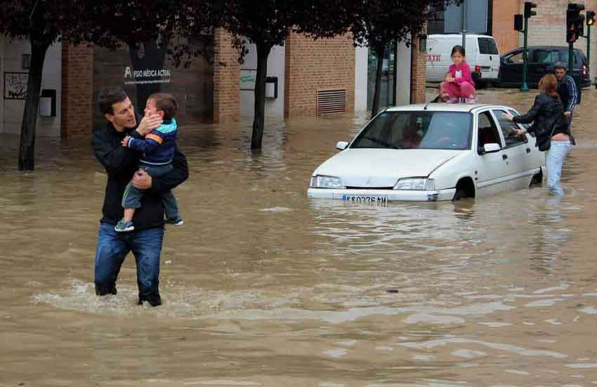 A man comforts a child rescued from a car, right, blocked on the roadside by water overflowing from the Arga River, in La Rochapea, near Pamplona northern Spain, Sunday, June 9, 2013. Heavy rains have affected northern Spain in the last few days with flooding particularly in Navarra province. (AP Photo/Carmelo Butini)