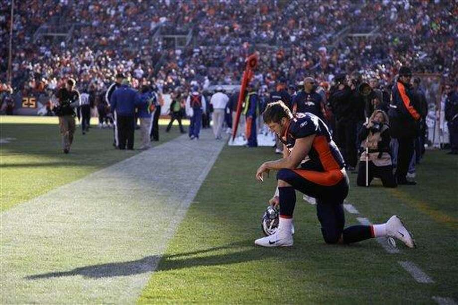 In this Dec. 11, 2011 file photo, Denver Broncos quarterback Tim Tebow prays in the end zone before the start of an NFL football game against the Chicago Bears,  in Denver. Peyton Manning is negotiating to join the Broncos, ESPN reported Monday, March 19, 2012.  Citing anonymous sources, ESPN said that the four-time MVP has instructed agent Tom Condon to negotiate the details of a deal with Denver.  The addition of Manning could well lead to Denver trading Tebow, even though the popular QB energized the Broncos in leading them to the playoffs last season despite some uneven play. (AP Photo/Julie Jacobson, File) Photo: ASSOCIATED PRESS / AP2011