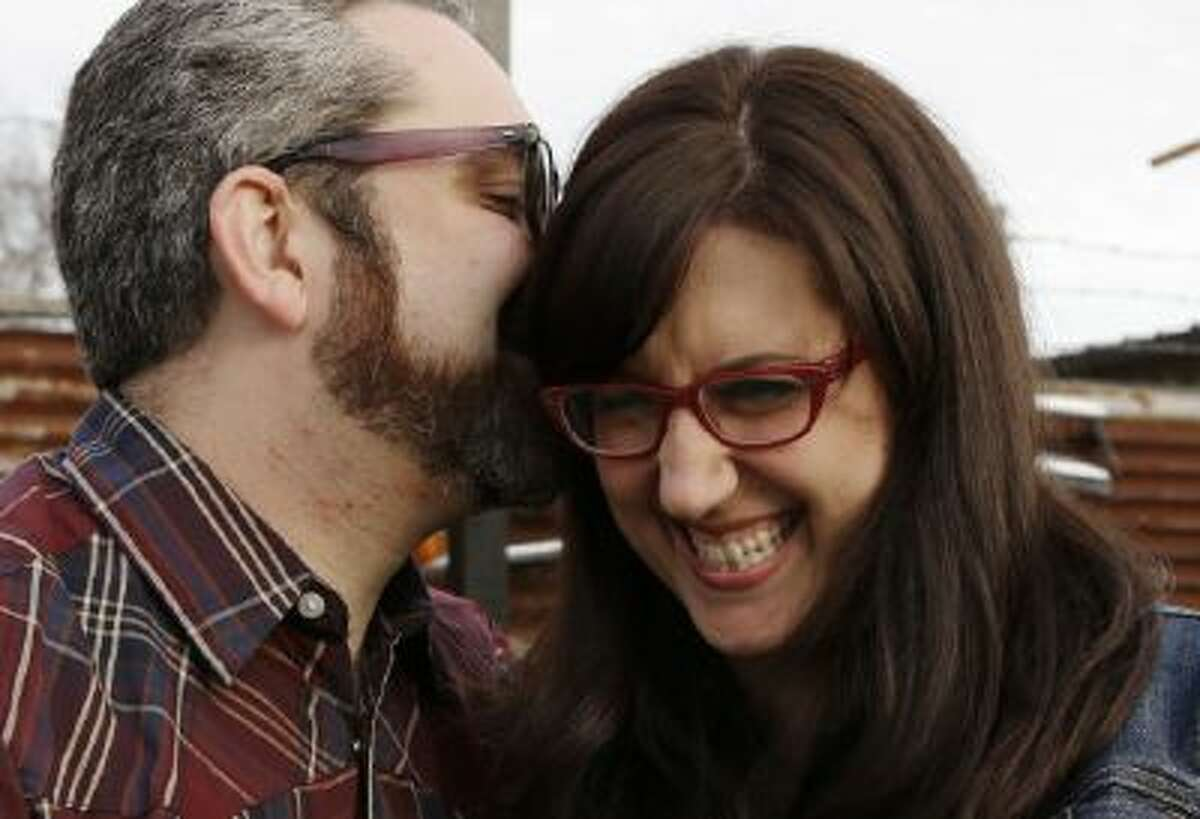 This Jan. 19, 2013 photo shows Nicole Buergers, right, and Brenden Macaluso snuggling at an eatery in Houston. In this age of online dating, virtual flirting and location-based hookup by app, these two are firm believers in three-dimensional serendipity nearly a year after their first encounter.