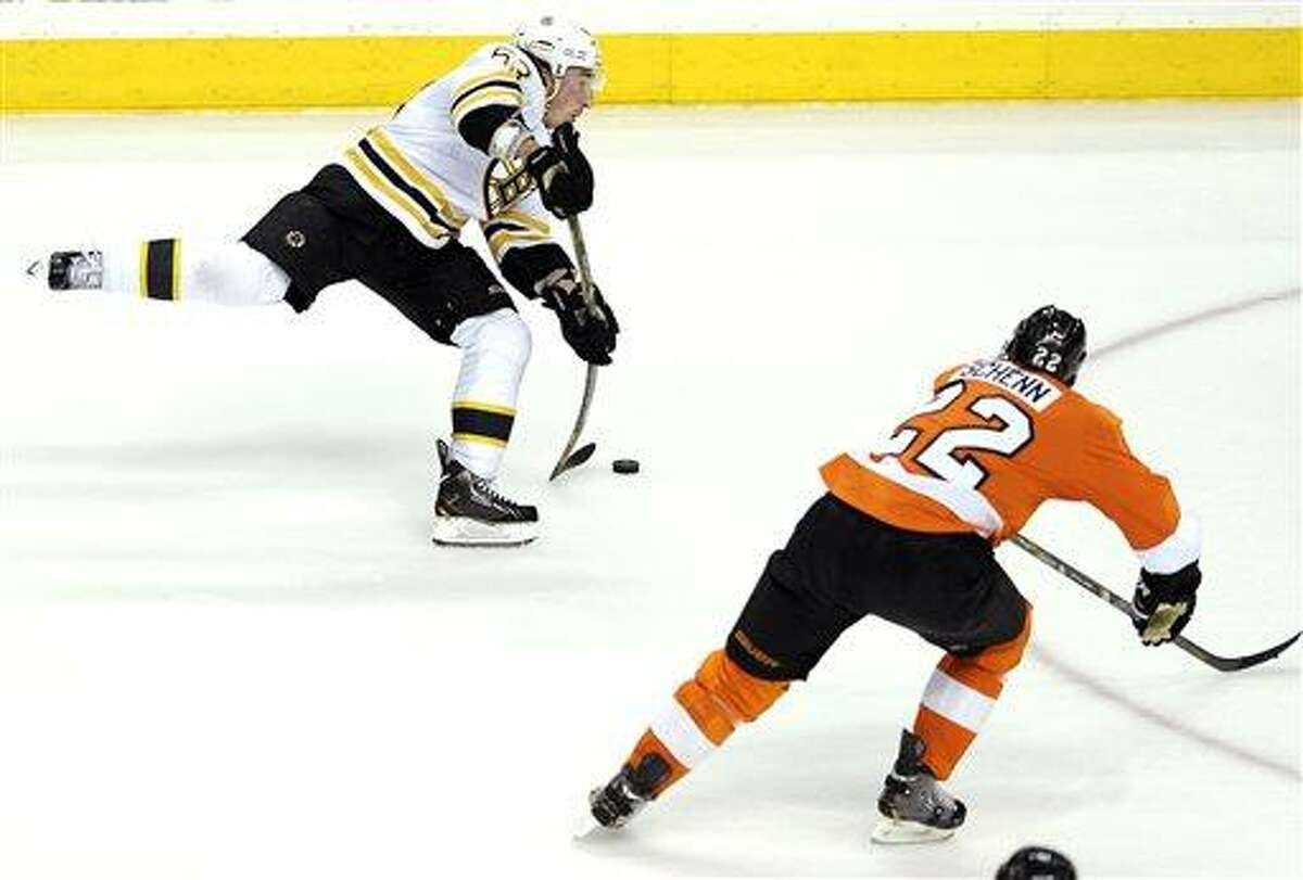 Boston Bruins' Brad Marchand (63) shoots on goal as Philadelphia Flyers' Luke Schenn (22) defends in the third period of an NHL hockey game, Saturday, March 30, 2013, in Philadelphia. The Flyers won 3-1. (AP Photo/Michael Perez)
