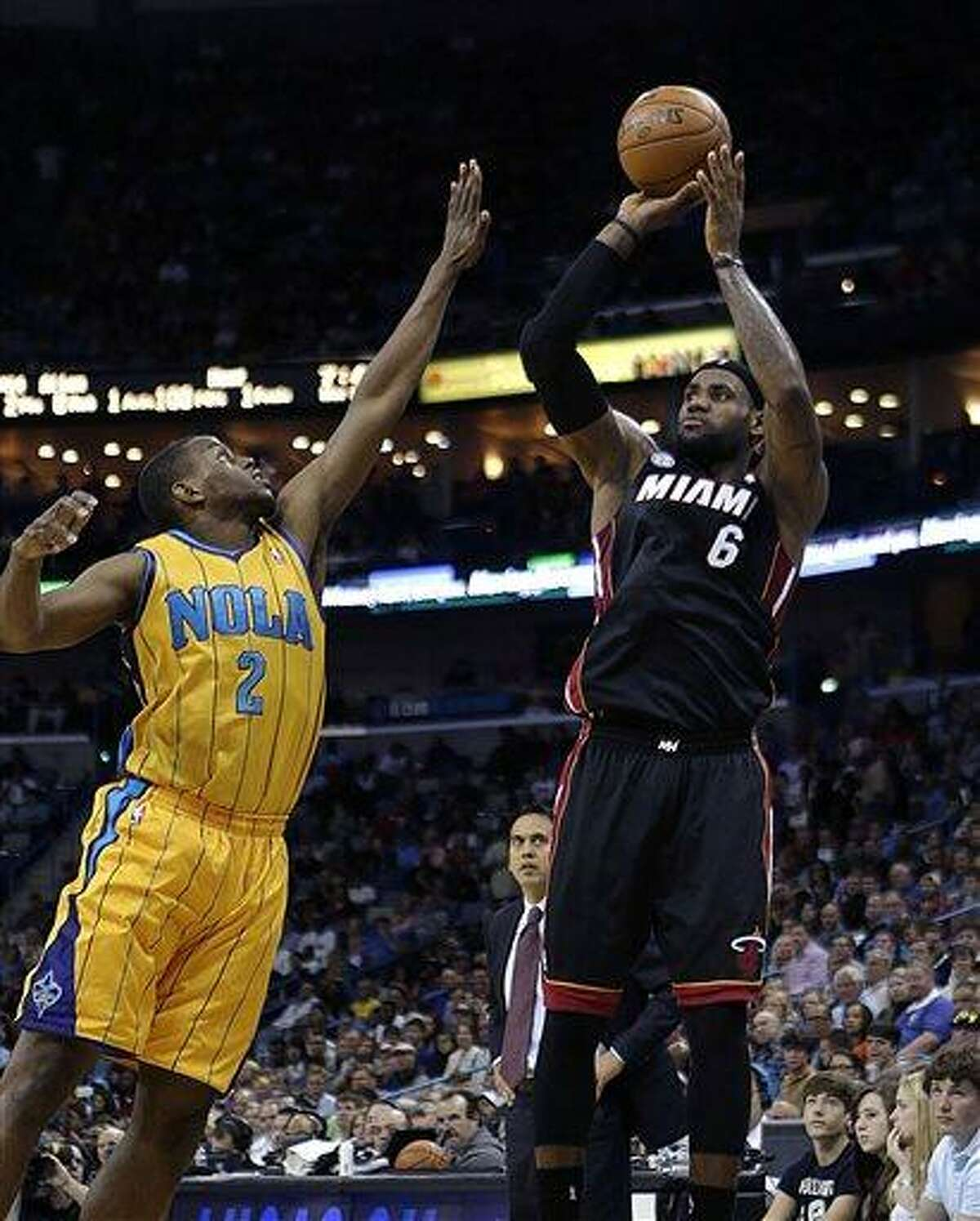 Miami Heat forward LeBron James (6) takes a 3-point shot in front of New Orleans Hornets forward Darius Miller (2) in the first half of an NBA basketball game in New Orleans, Friday, March 29, 2013. (AP Photo/Gerald Herbert)