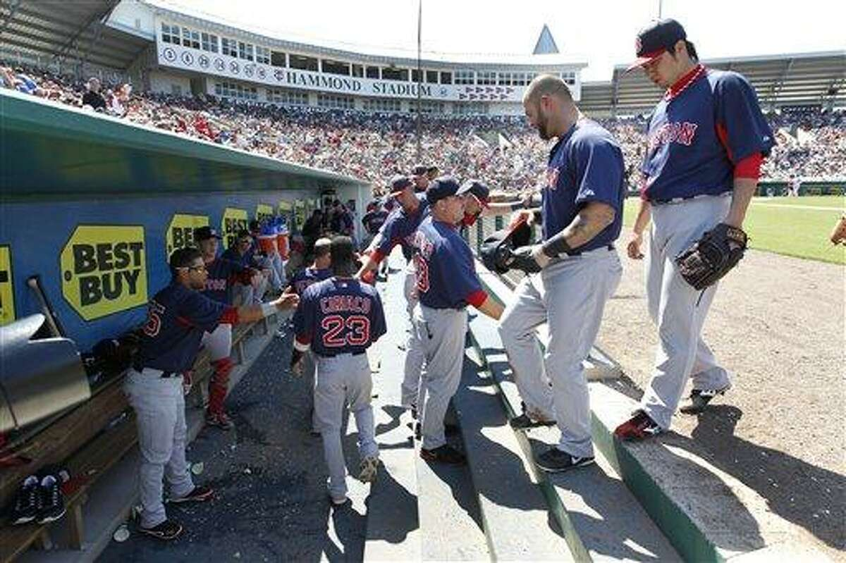 Boston Red Sox players return to the dugout during an exhibition spring training baseball game against the Minnesota Twins in Fort Myers, Fla., Friday, March 29, 2013. (AP Photo/Elise Amendola)