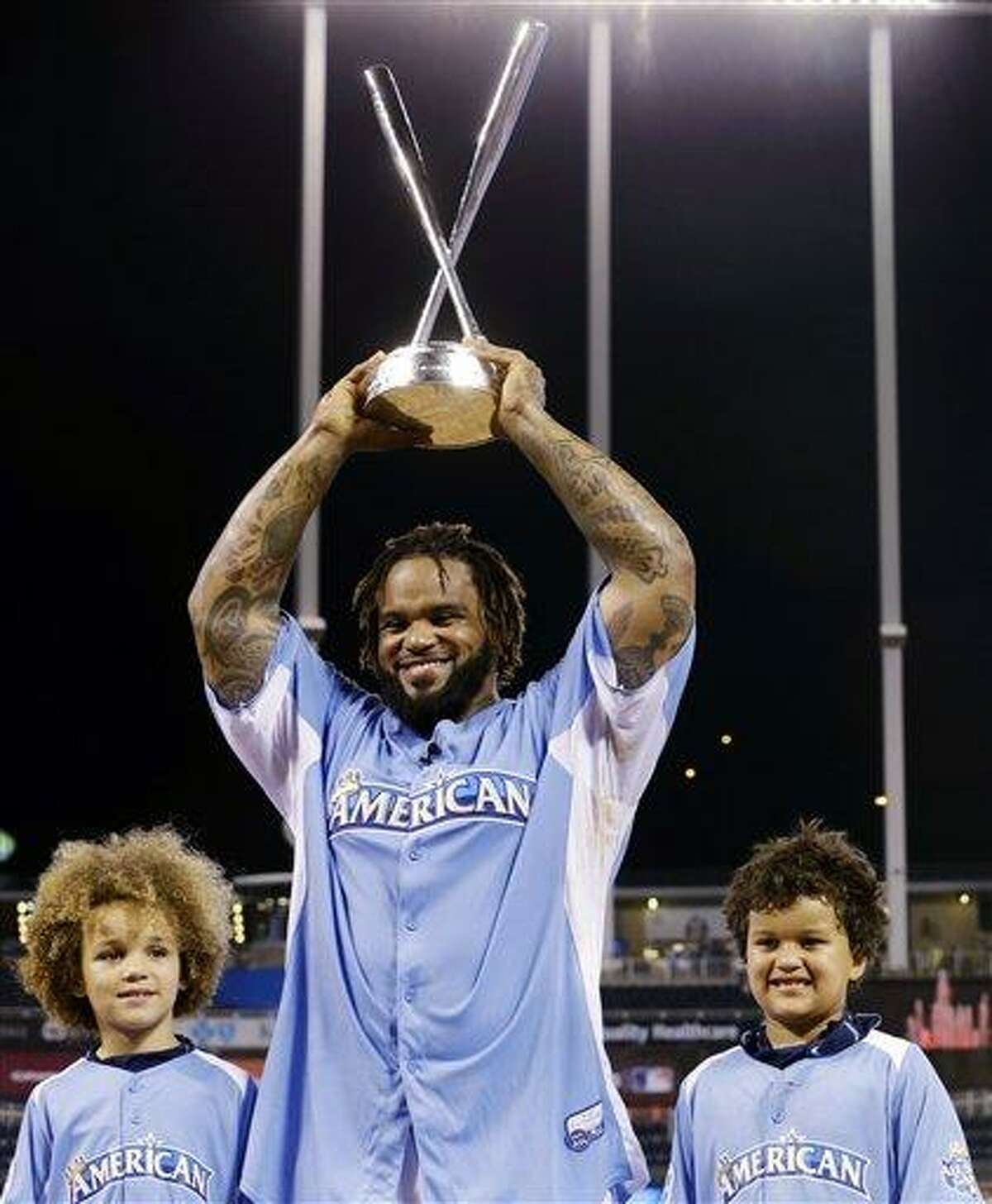 American League's Prince Fielder, of the Detroit Tigers, poses with his children Jaden, left, and Haven after receiving the MLB All-Star baseball Home Run Derby trophy, Monday, July 9, 2012, in Kansas City, Mo. (AP Photo/Charlie Riedel)