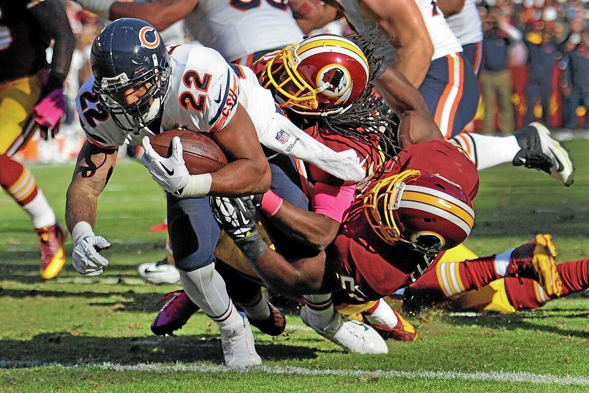 Chicago Bears running back Matt Forte (22) drags Washington Redskins strong safety Brandon Meriweather, center, and inside linebacker London Fletcher, right, into the end zone for a touchdown during the second half of Sunday's game in Landover, Md.