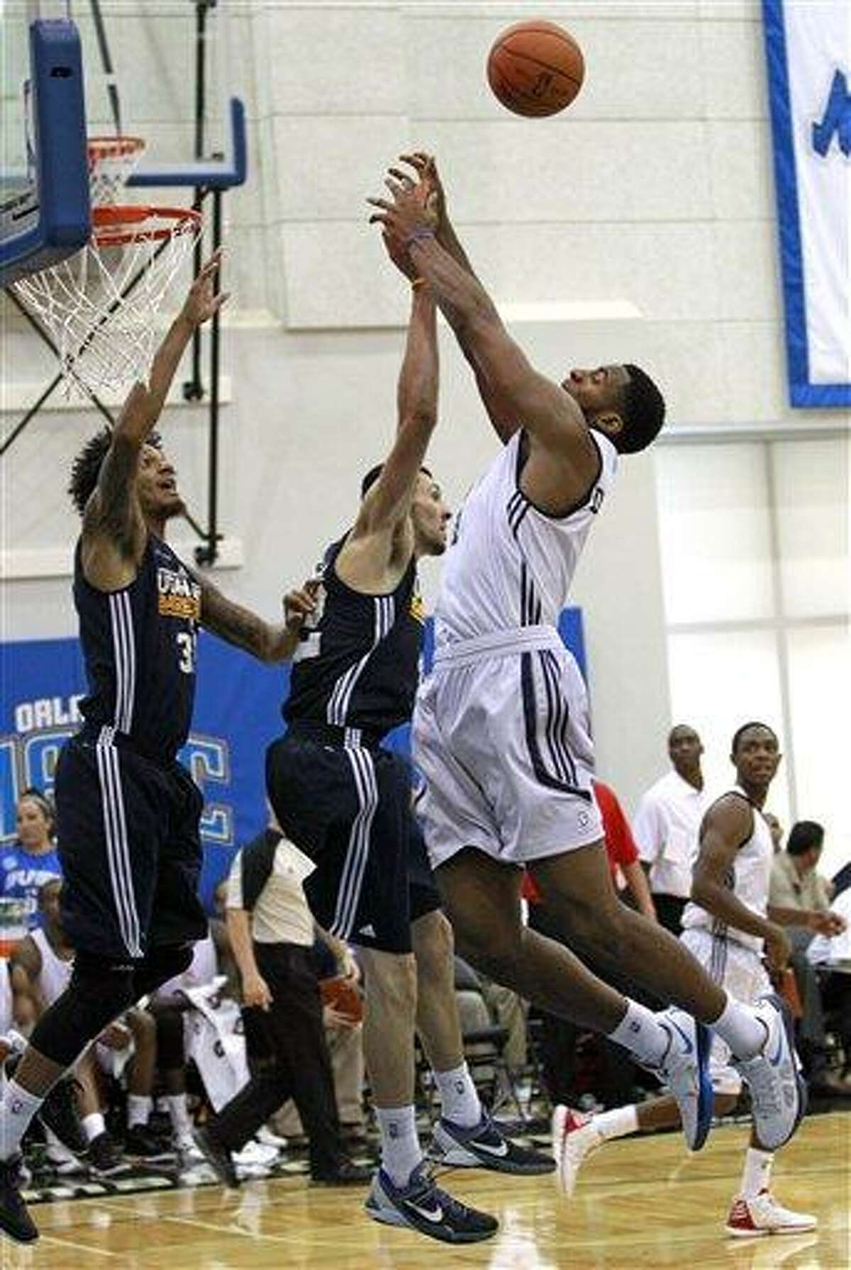 Detroit Pistons' Andre Drummond, right, goes for a rebound against Utah Jazz's Deron Washington, left, and Tony Gaffney, center, during an NBA summer league basketball game, Monday, July 9, 2012, in Orlando, Fla. (AP Photo/John Raoux)
