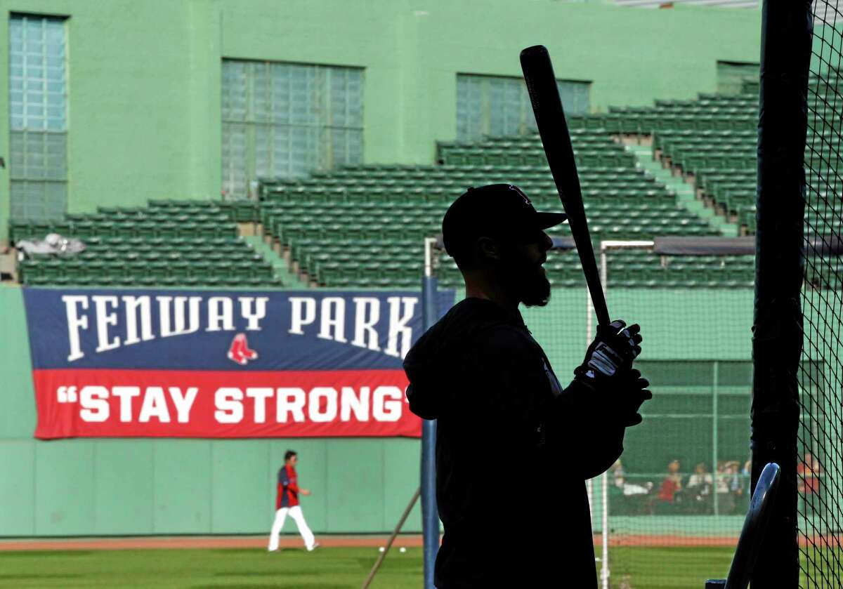 Boston Red Sox second baseman Dustin Pedroia waits for his turn in the batting cage during practice Monday at Fenway Park in Boston. The Red Sox will face the St. Louis Cardinals in Game 1 of the World Series on Wednesday.