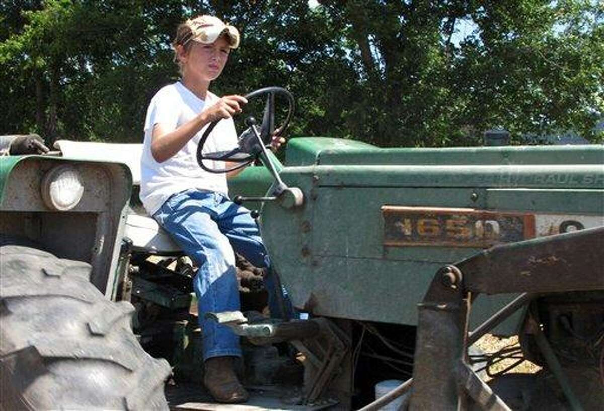Jacob Mosbacher, 10, guides a tractor through a bean field June 20 on his grandparents' property near Fults, Ill. Agriculture organizations and federal lawmakers from farm states succeeded last spring in convincing the U.S. Labor Department to drop proposals limiting farm work by children such as Jacob, whose parents say such questions of safety involving kids should be left to parents. Associated Press