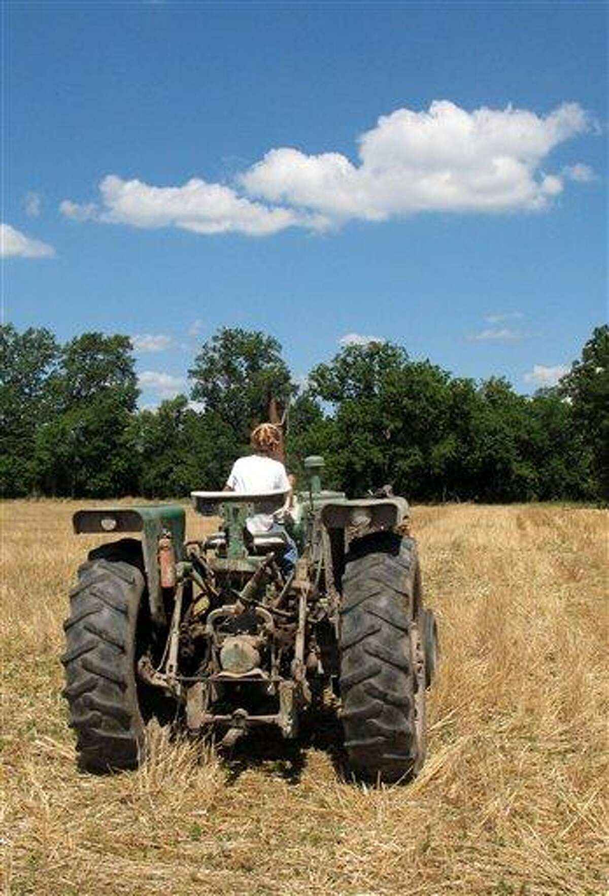 Jacob guides a tractor through a bean field June 20 on his grandparents' property near Fults, Ill. Associated Press