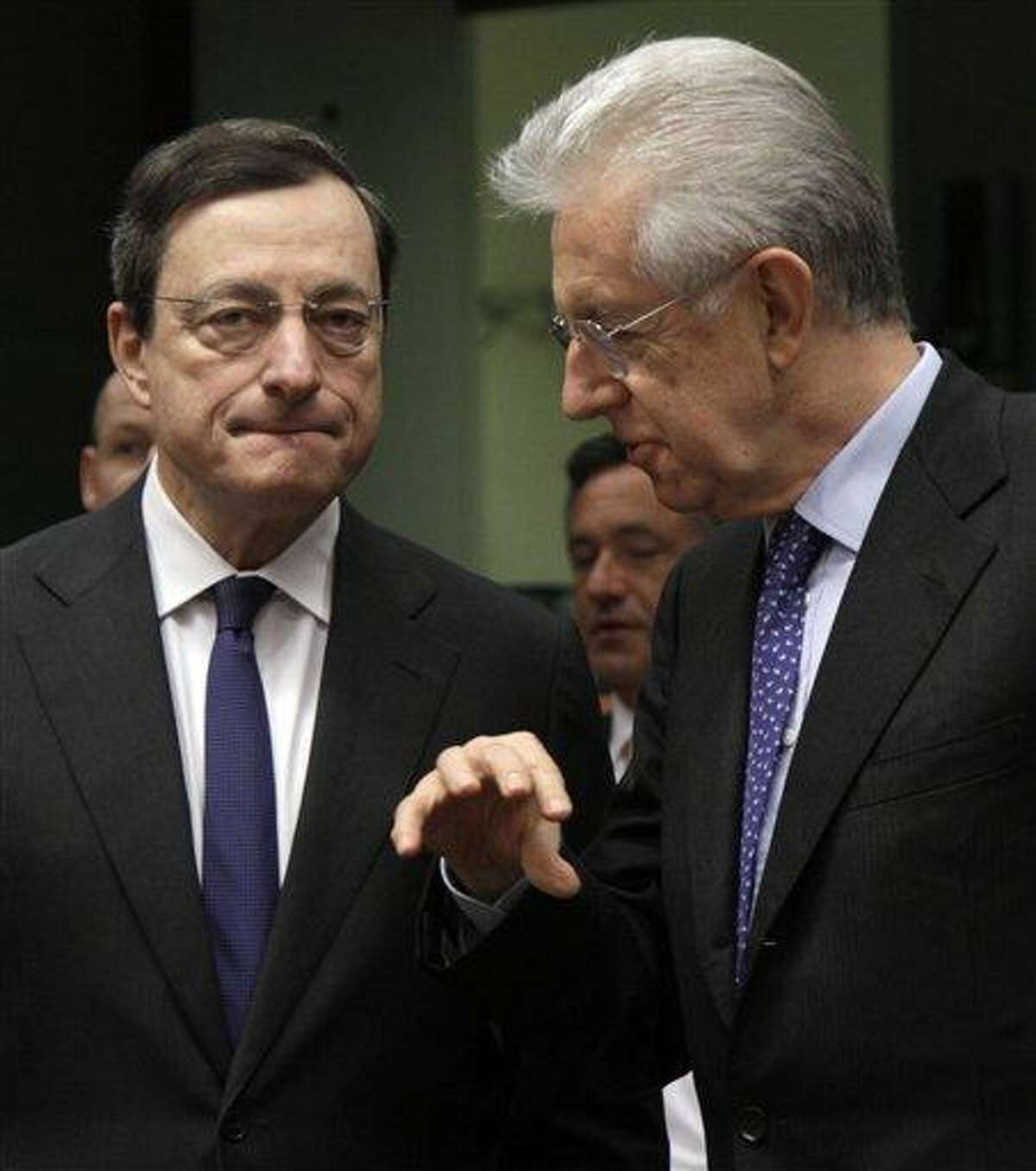 Italian Prime Minister Mario Monti, right, speaks with European Central Bank President Mario Draghi during a meeting of eurozone finance ministers at the EU Council building in Brussels earlier this month. Associated Press
