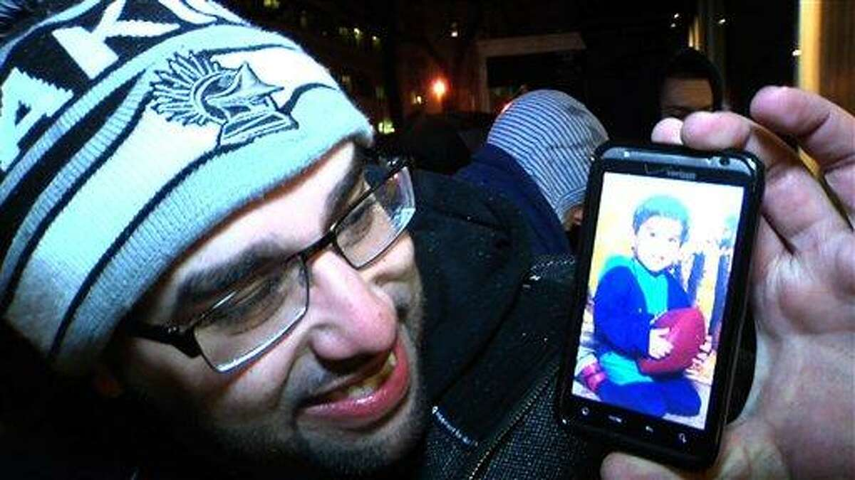"""Sean Rivera poses with a photo Feb. 24 that he loaded onto his cellphone that shows him, as a toddler, with his first pair of Air Jordan shoes. Rivera, a 28-year-old college counselor from Chicago, was one of about 60 """"sneakerheads"""" who camped outside a Nike shoe store in Chicago in the freezing rain, waiting for the release of limited edition shoes. Rivera and other sneakerheads collect new and vintage shoes, many of them limited edition sports shoes that carry the names of basketball greats such as Michael Jordan and Lebron James. The craze started back in the 1980s with the release of the first Air Jordan shoe, but has gotten more attention recently as sneakerheads have clamored for shoes and caused riots in some cities. Associated Press"""