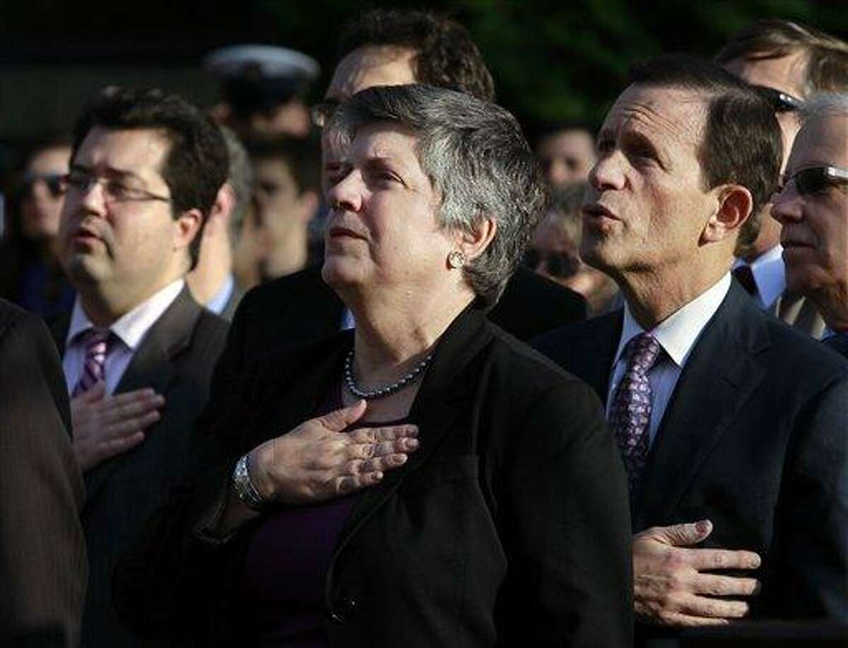 In this file photo, U.S. Homeland Security Secretary Janet Napolitano, center, and Mass. Treasurer Steven Grossman, right, place their hands over their hearts along with others during the playing of the national anthem during ceremonies held to add three new names to Northeastern University's Veterans Memorial, in Boston Nov. 12. (AP Photo/Steven Senne)