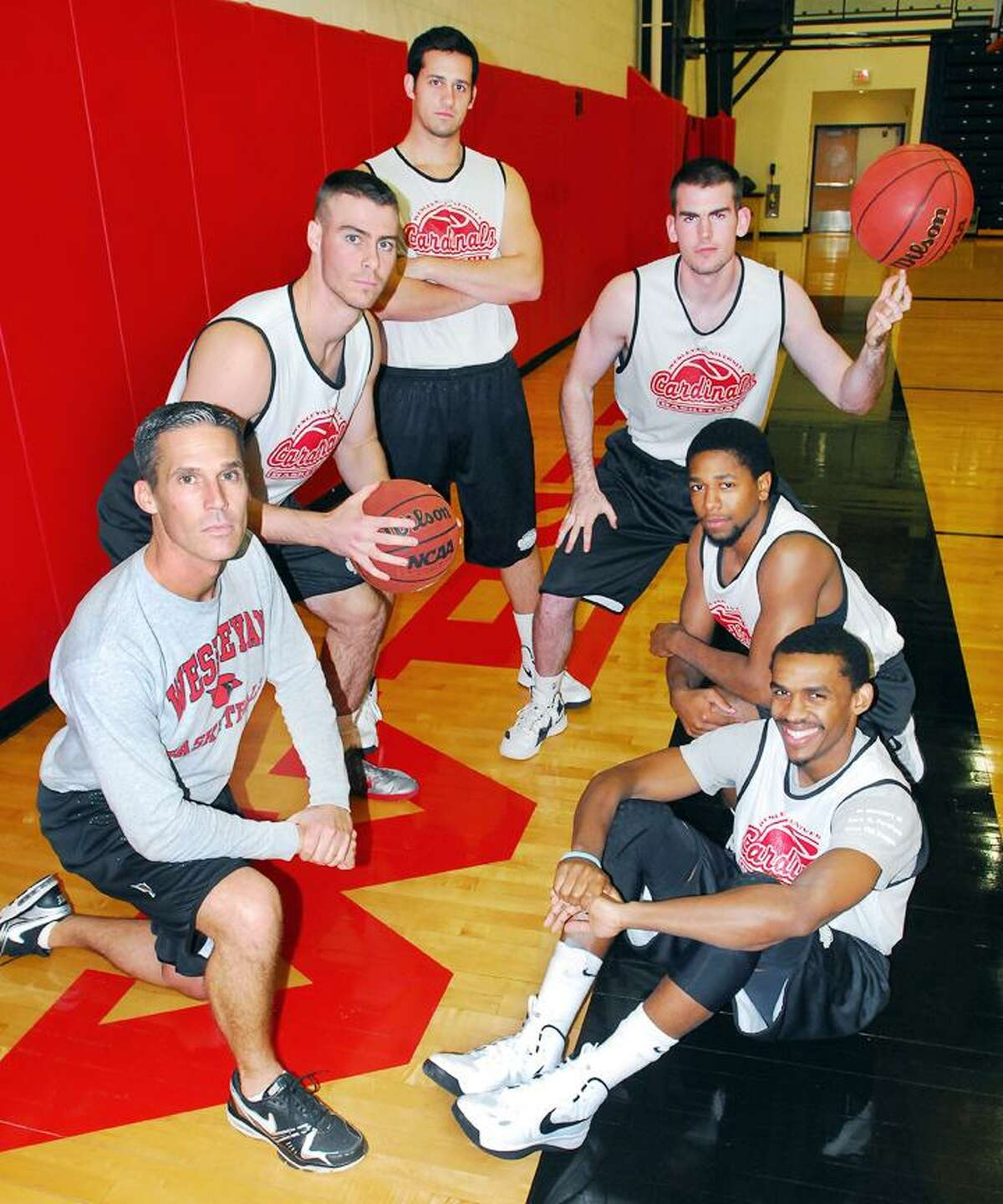 Catherine Avalone/The Middletown Press Wesleyan men's basketball coach Joe Reilly, left, and senior captains (clockwise from the left) Mike Callaghan, Matt Hogan, Greg St. Jean, Derick Beresford and Shasha Brown. The five seniors are all members of Reilly's first recruiting class.