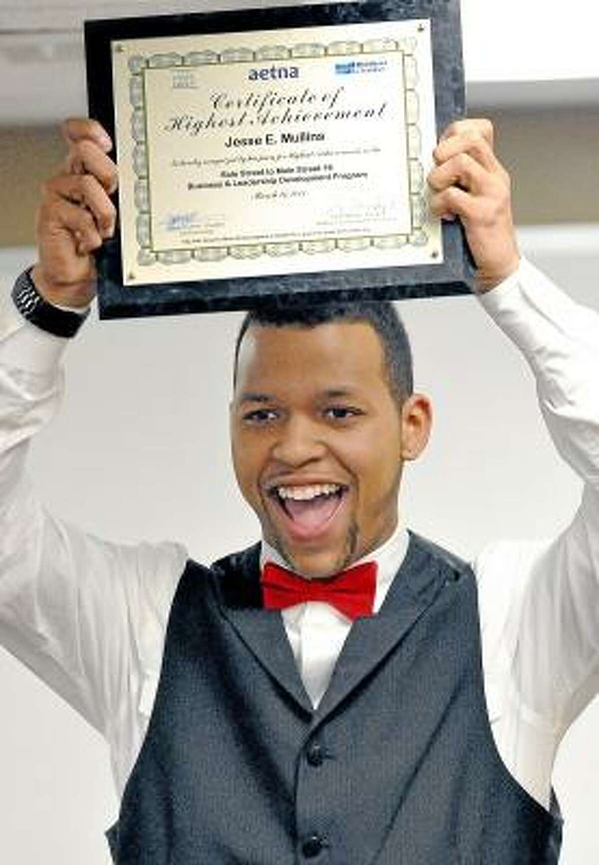 Catherine Avalone/The Middletown Press Jesse E. Mullins raises after learning he received the Certificate of Highest Achievement from Side Street to Main Street Business & Leadership Development Program Wednesday evening during their sixteenth graduation sponsored by the Middlesex County Chamber of Commerce at 393 Main Street in Middletown. The program is designed to assist minority small business owners in the community who have not had formal business training. The fee for the program is normally over $5,000 per individual but because of a grant from Aetna, there is no charge for qualified participants. Mullins was