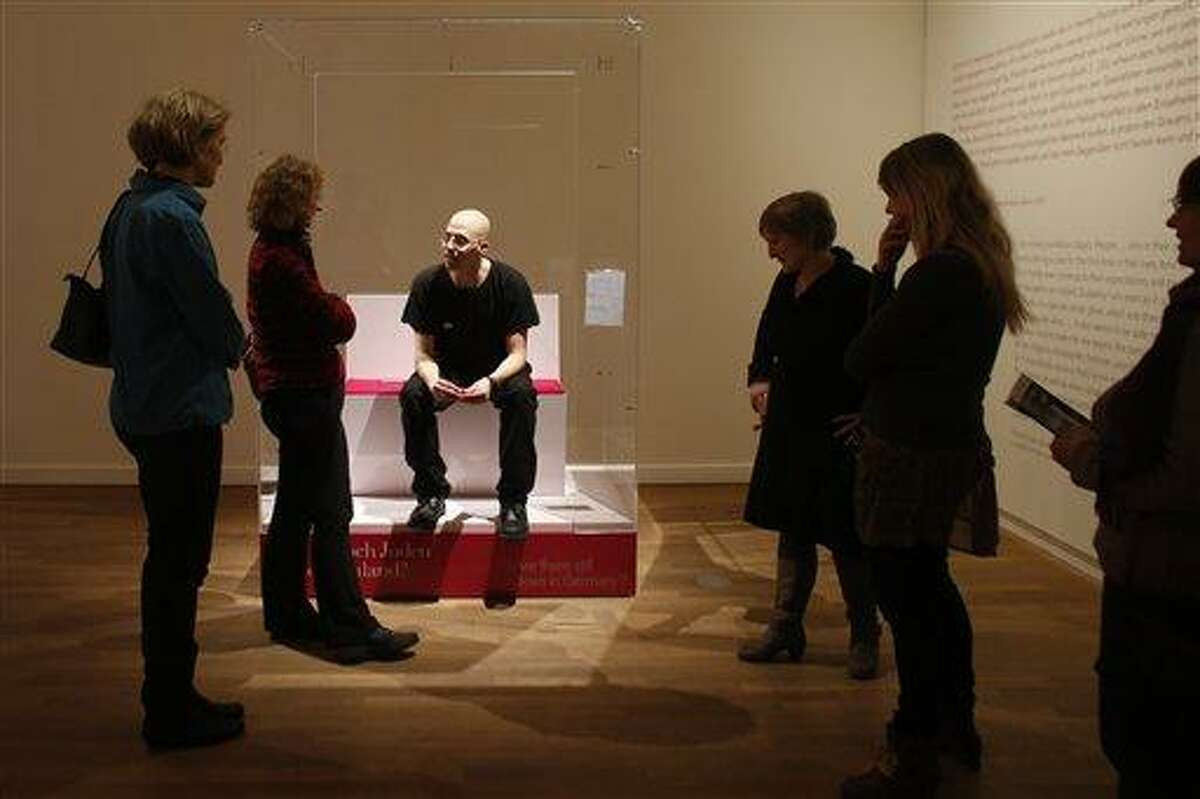 FILE - In this March 22, 2013 file photo, visitors surround Ido Porat, the first person acting as the 'Jew in a glass box', on the first day of the exhibition