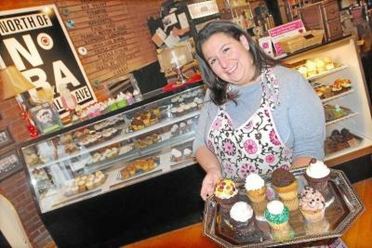 Carrie Carell, owner of NoRA Cupcake Company on Main Street in Middletown displays a couple of favorites such as the Irish Car Bomb, Adult Twinkie and the Funky Monkey. Carell will receive the Hometown Main Street Business of the Year at the Chamber of Commerce first ever Small Business of the Year Awards. NoRA will celebrate one year of business on New Year's Eve. Catherine Avalone/The Middletown Press