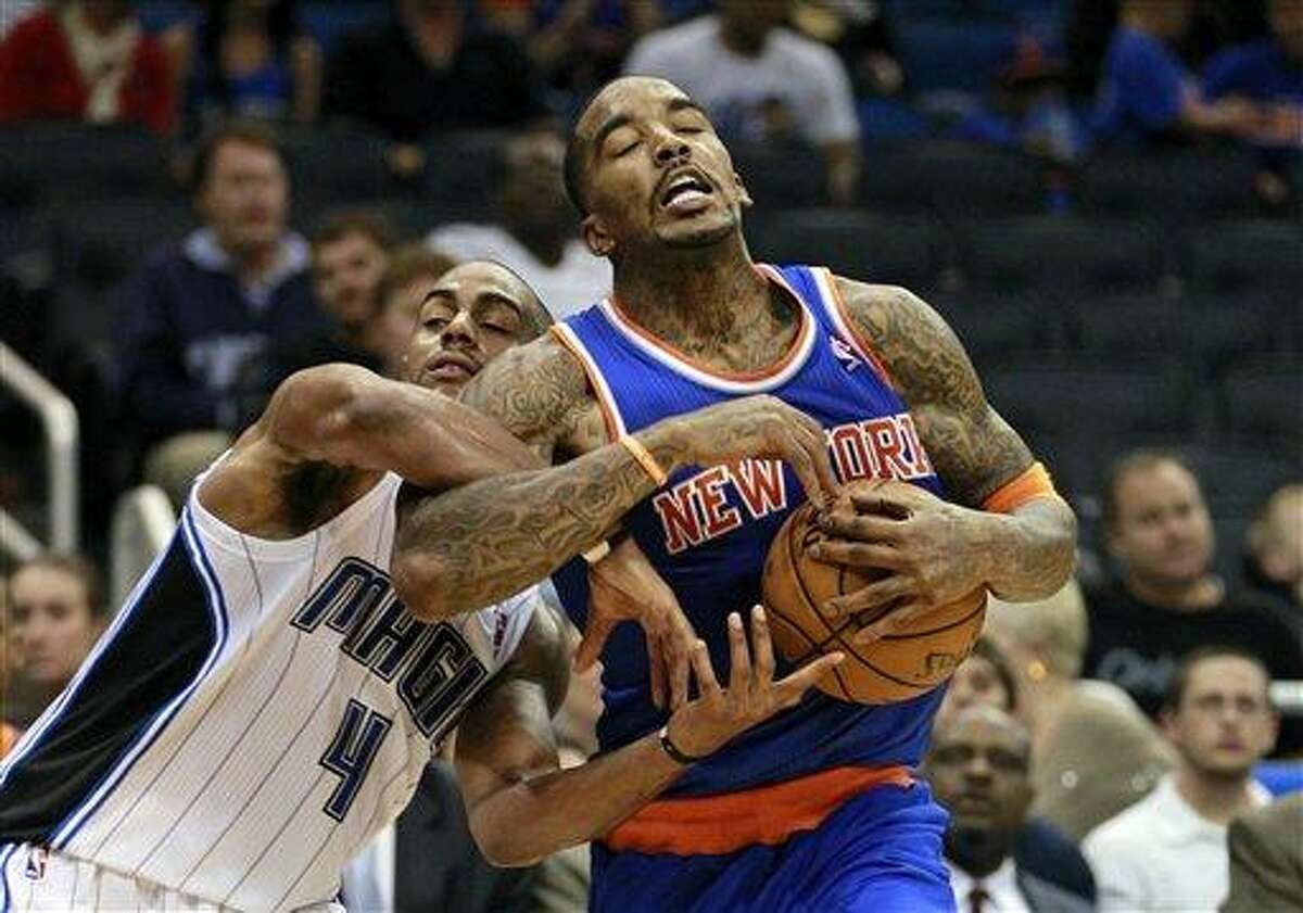 Orlando Magic's Arron Afflalo (4) and New York Knicks' J.R. Smith fight for possesion of the ball during the second half of an NBA basketball game, Tuesday,Nov. 13, 2012, in Orlando, Fla. The play resulted in a jump ball and New York won the game 99-89. (AP Photo/John Raoux)