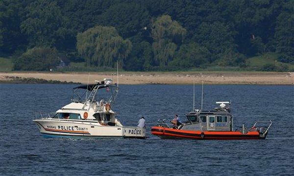 Two police boats are stationed Saturday near the opening to the Long Island Sound in Lloyd Harbor, N.Y., not far from where a boat capsized on July 4. Investigators are trying to learn more about the crucial seconds before a yacht capsized off Long Island, killing three children and leaving 24 others scrambling for their lives. Associated Press