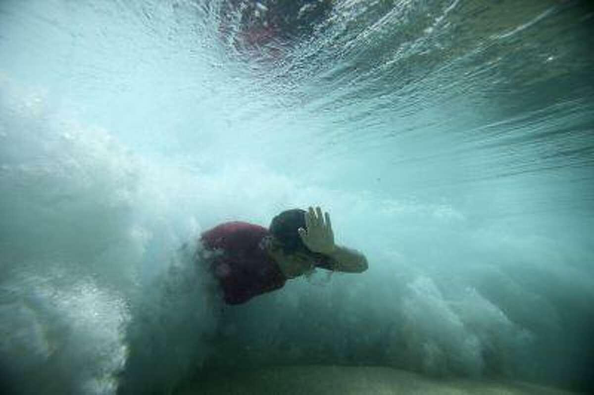 A bodysurfer punches through a wave at the Ehukai sandbar near the surf break known as 'Pipeline' on the North Shore of Oahu, Hawaii March 20, 2013.