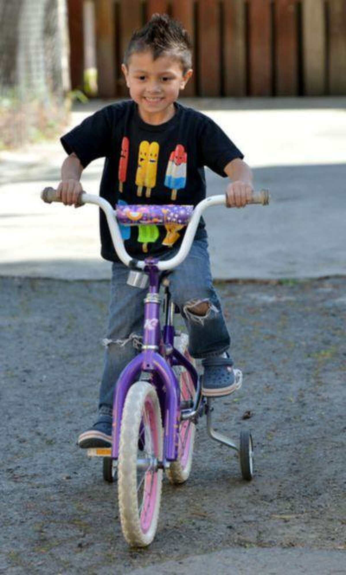Julian Meija-Blagovic, 4, of Martinez, rides a pink and white bike that his parents bought for him at a garage sale in Martinez, Calif., on Saturday March 23, 2013. His parents, Jorge Meija and Lisa Blagovic, are trying to raise their kids with respect and balance of gender.