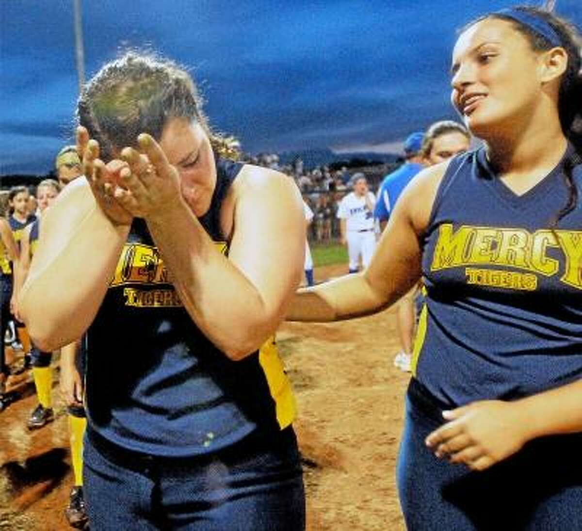 Catherine Avalone/The Middletown Press Mercy senior captain and catcher Tyler Keegan is consoled by junior Abigayle LaRosa following their 1-0 loss to Southington at Frank Biondi Softball Field at West Haven High School Sunday night in the Class LL State Championship game.