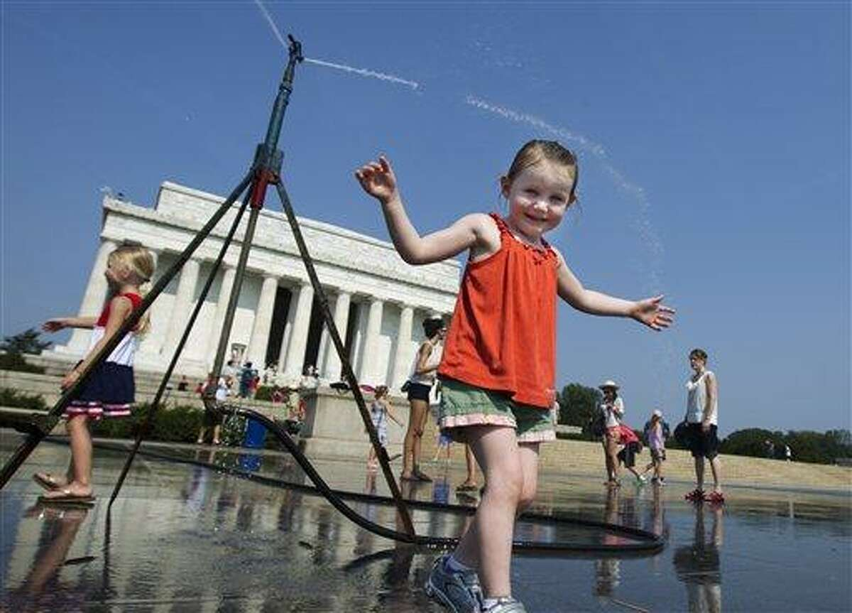 Sophie, 3, from Connecticut, frolics with a water sprinkler set up at the National Mall near the Lincoln Memorial, rear, in Washington Saturday. Associated Press
