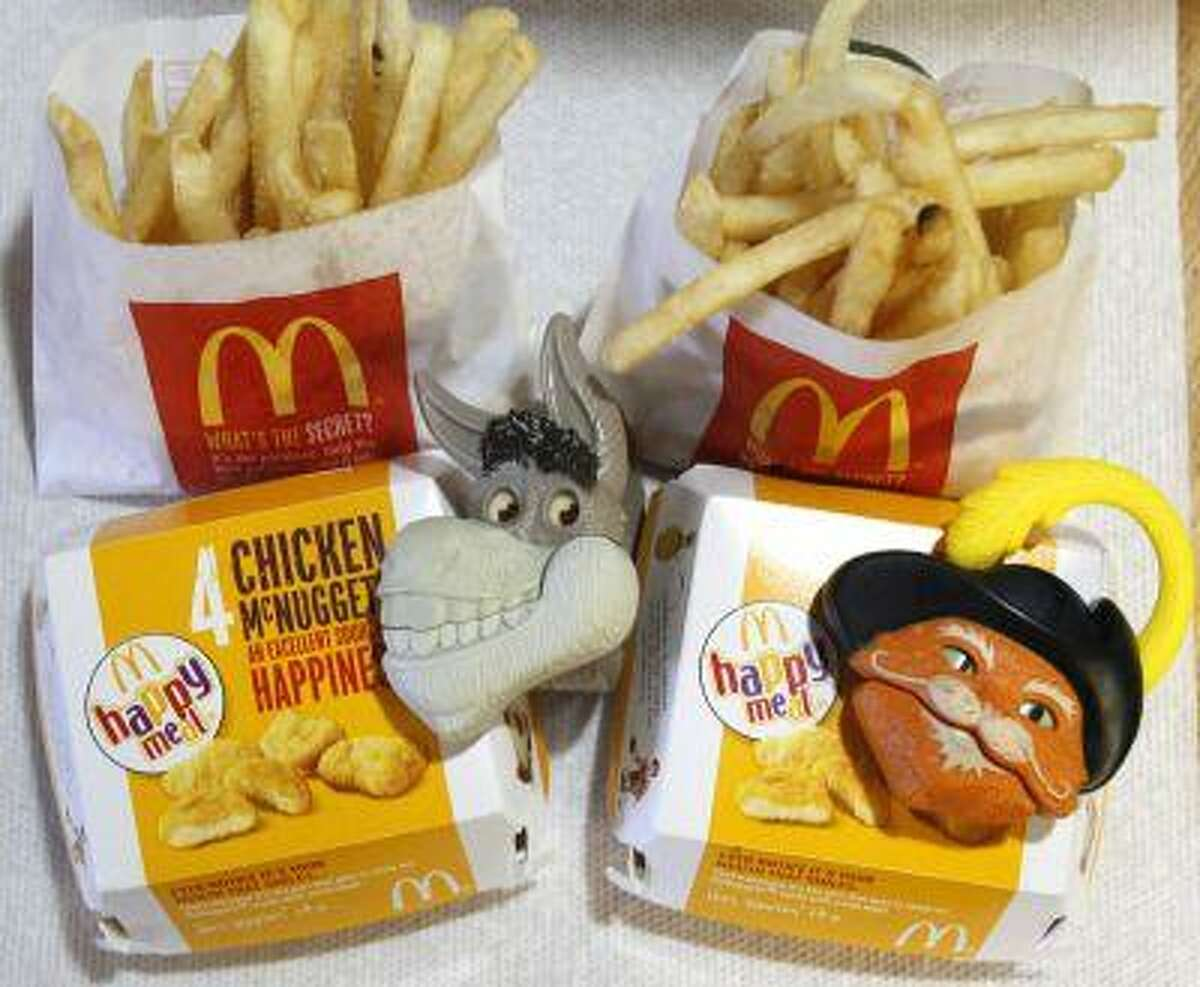 Two McDonald's Happy Meals with toy watches fashioned after the characters Donkey and Puss in Boots from the movie
