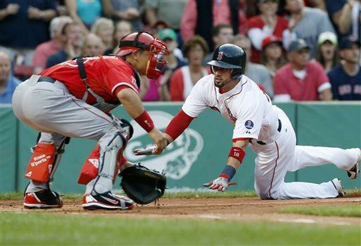 Boston Red Sox's Shane Victorino, right, scores on a double by Jonny Gomes as Los Angeles Angels' Hank Conger waits for the throw in the first inning of the second game of a baseball doubleheader in Boston, Saturday, June 8, 2013. (AP Photo/Michael Dwyer)