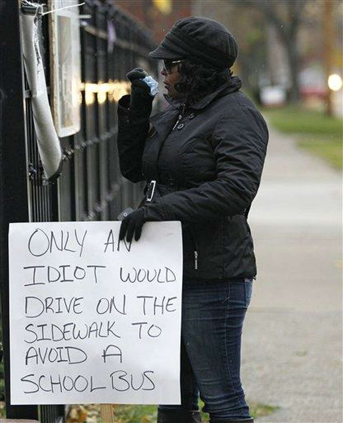 Shena Hardin wipes her nose as she holds up a sign to serve a highly public sentence Tuesday, Nov. 13, 2012, in Cleveland, for driving on a sidewalk to avoid a Cleveland school bus that was unloading children. A Cleveland Municipal Court judge ordered 32-year-old Hardin to serve the highly public sentence for one hour Tuesday and Wednesday. (AP Photo/Tony Dejak)
