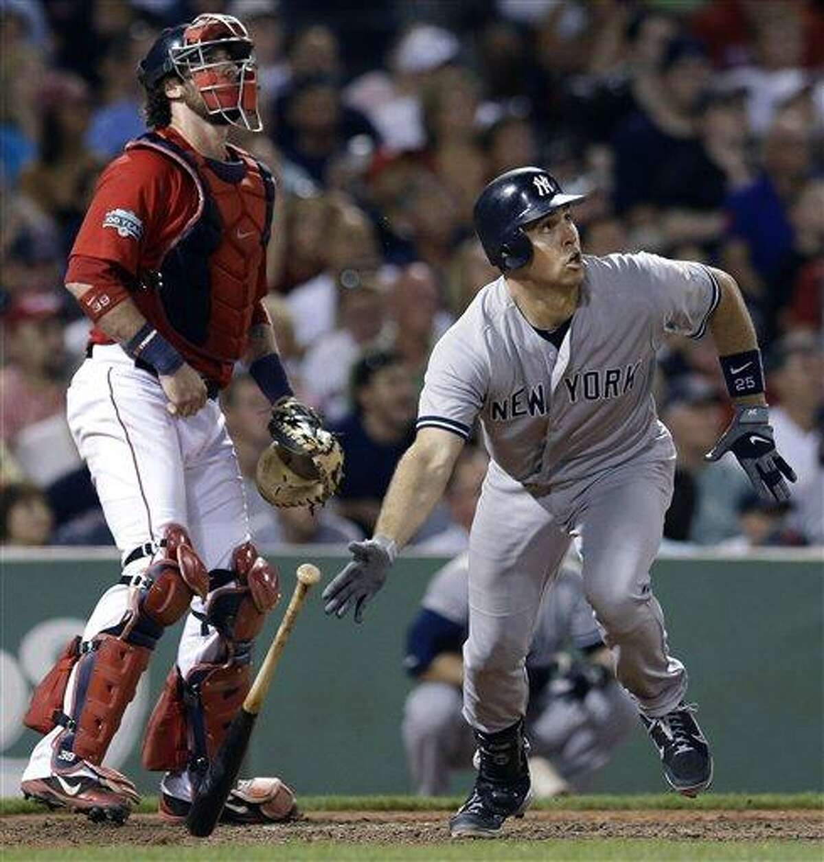 New York Yankees' Mark Teixeira watches his two-run triple next to Boston Red Sox catcher Jarrod Saltalamacchia during the seventh inning of a baseball game at Fenway Park in Boston on Friday, July 6, 2012. The Yankees won 10-8. (AP Photo/Elise Amendola)