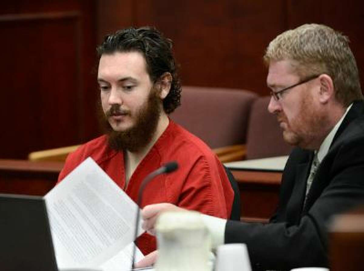 James Holmes, left, glances over an advisement as his defense attorney, Daniel King, turns the pages in court Tuesday morning June 04, 2013 for an advisement hearing at the Arapahoe County Justice Center. Holmes is accused of killing 12 people and injuring 70 others in a shooting rampage at an Aurora theater, July 20th, 2012. The court accepted James Holmes plea of not guilty by reason of insanity and has ordered a sanity evaluation at the Colorado Mental Health Institute of Pueblo.