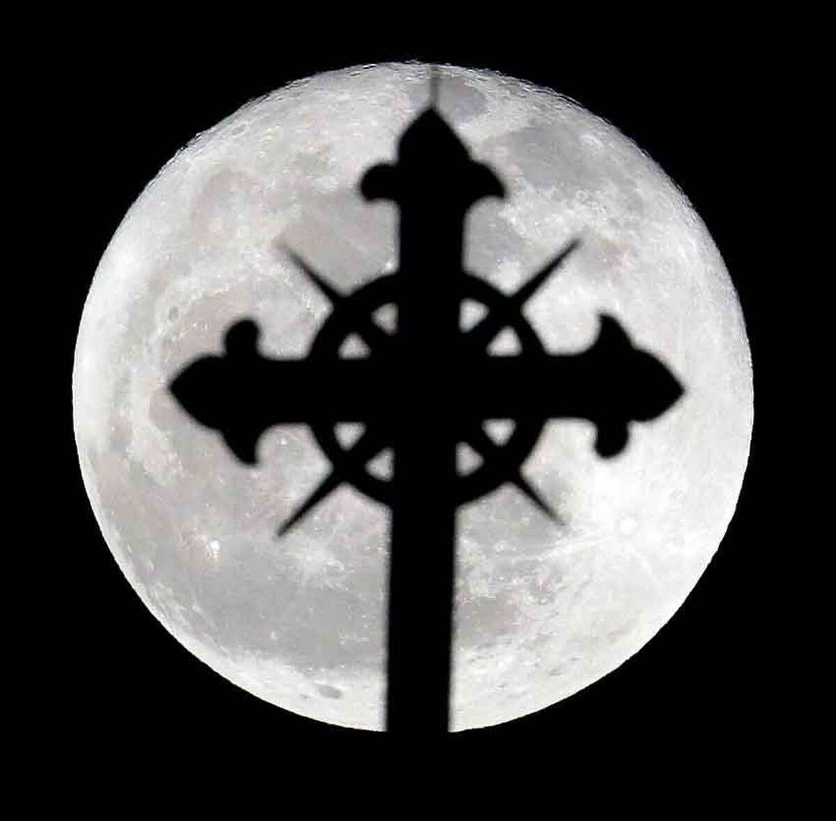 A full moon rises behind a cross on top of Saint Nicholas Catholic Church in the Heights neighborhood of Jersey City, N.J., Wednesday, March 27, 2013. Catholics are observing Holy Week, which is the final week of the Lent period before Easter. (AP Photo/Julio Cortez)