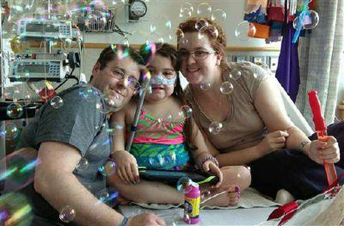 FILE - In this May 30, 2013 file photo provided by the Murnaghan family, Sarah Murnaghan, center, celebrates the 100th day of her stay in Children's Hospital of Philadelphia with her father, Fran, left, and mother, Janet. A federal judge in Philadelphia on Wednesday, June 5, 2013 made the dying 10-year-old eligible to seek donor lungs from an adult transplant list. (AP Photo/Murnaghan Family, File)
