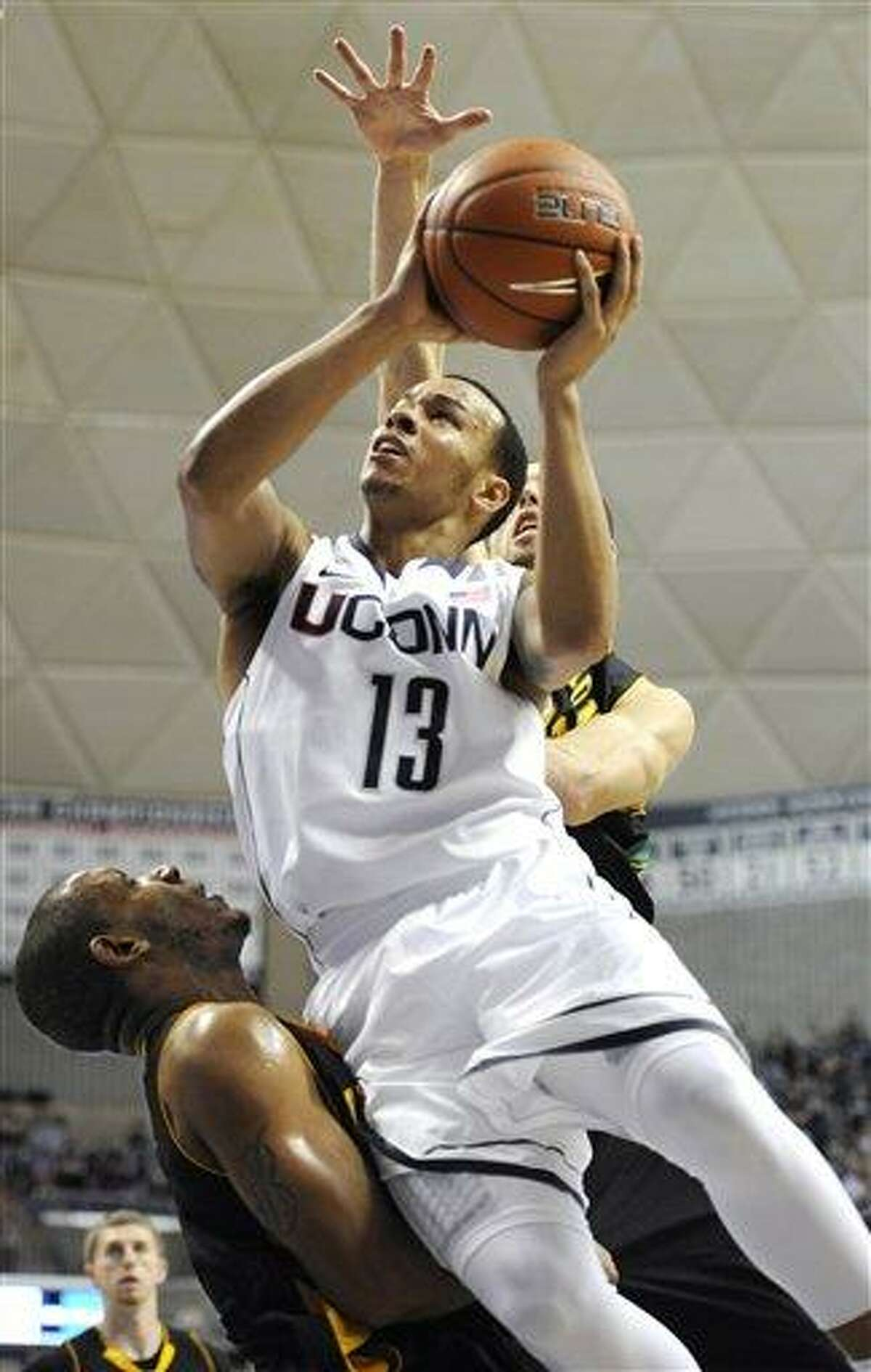 Connecticut's Shabazz Napier (13) shoots over Vermont's Trey Blue, bottom, in the second half of an NCAA basketball game in Storrs, Conn., Tuesday, Nov. 13, 2012. Vermont's Ethan O'Day, right, defends on the play. No. 23 Connecticut won 67-49. Napier scored 13 points. (AP Photo/Jessica Hill)