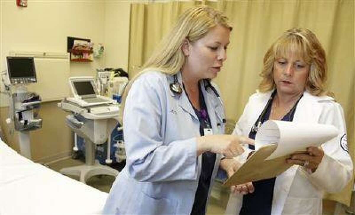 Nurse practitioners Michele Knappe, left, and Julie Zimmer go over a patients chart at Ingalls Family Care Center in Flossmoor, in the Ingalls Urgent Aid free-standing emergency room, Tuesday, June 4, 2013, in Flossmoor, Ill. Illinois lawmakers this spring rebuffed a variety of proposals that would have given more authority to nurses ahead of a surge of patients newly insured under President Obama's health law. Patients are expected to find widespread shortages of primary care doctors in one-fifth of Illinois counties. Some experts say nurses with advance degrees can safely help fill the gap if legal barriers are removed. (AP Photo/M. Spencer Green)