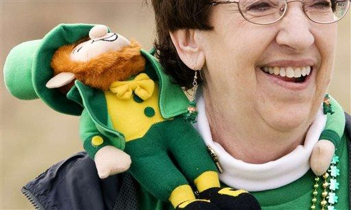 Donna Schneider of West Bend, Wis. shares a laugh with friends as she has a little leprechaun across her shoulder during the St. Patrick's Day Parade in the Town of Erin on Saturday, March 17, 2012. (AP Photo/West Bend Daily News, John Ehlke)