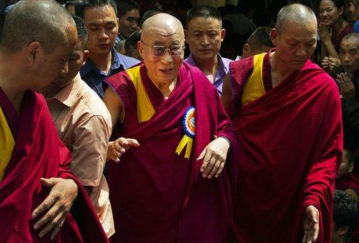Tibetan spiritual leader, the Dalai Lama, center, is escorted by Tibetan monks as he leaves Tsuglakhang temple in Dharmsala, India, Friday. The Dalai Lama celebrates his 77th birthday with festivities held for the entire day at the temple complex. Associated Press